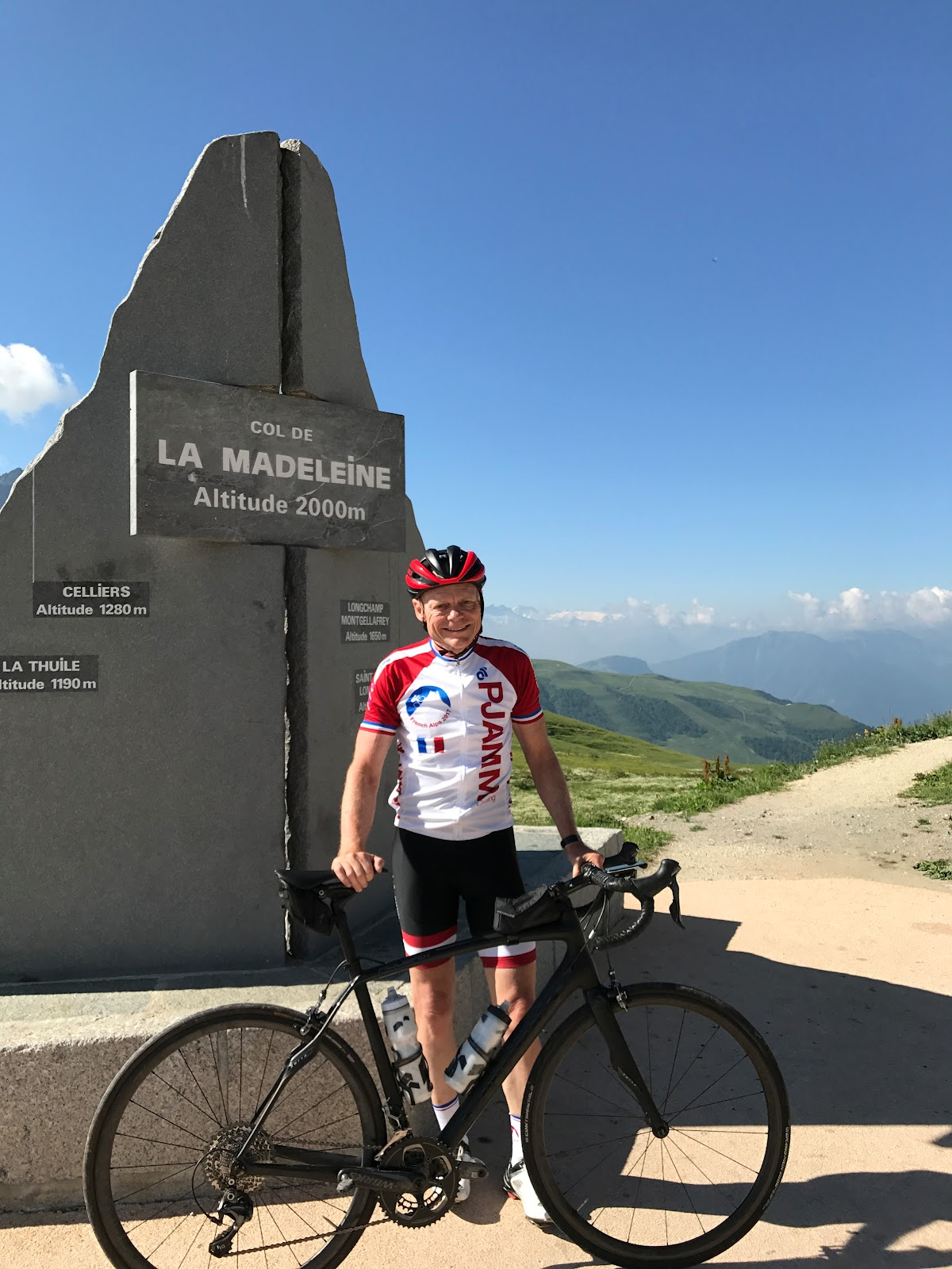 Cycling the greatest climbs - Col de Madeleine from La Chambre  - cyclists with bike at col monument