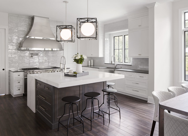 chic modern kitchen with distressed grey center island and surrounding white shaker cabinetry. a thick white countertop island steals the show in this kitchen design
