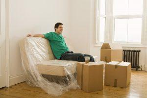 Man sitting in a new home ready for unpacking.