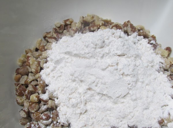 Combine 1/2 cup flour with the chopped black walnuts,then