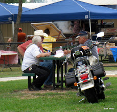 Photo: David Hannah, Mary Lou Pasley, and Art Morris eating.  Ken Smith's motorcycle.   HALS 2009-0919