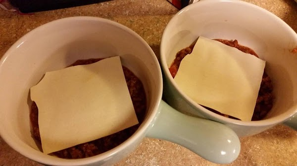Break one sheet of oven-ready lasagne in half and place on meat sauce.