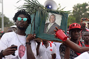 Supporters of the ruling All Peoples Congress carry a mock coffin decorated with a picture of Julius Maada Bio, a presidential candidate for the Sierra Leone People's Party, during a rally ahead of the March 7 presidential election in Makeni, Sierra Leone on March 5 2018.