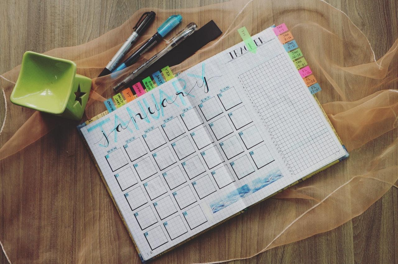 A handwritten planner with the January pages open on a wooden table