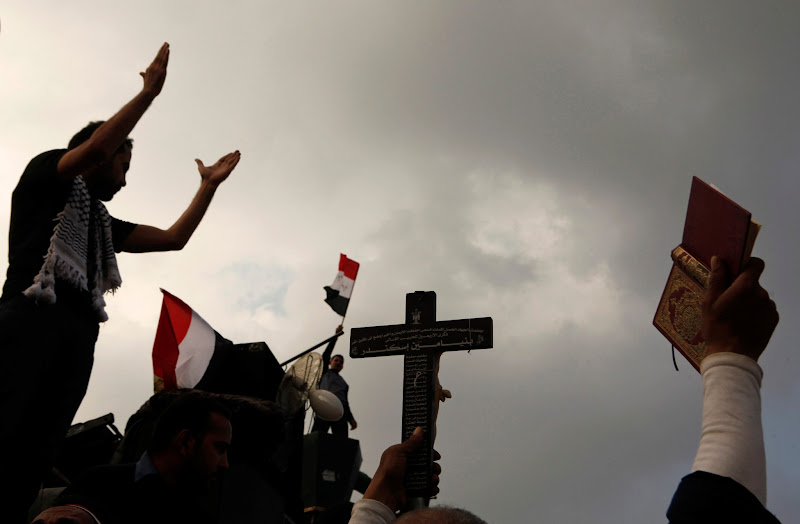Photo: A protester carries a cross and a Koran as thousands of demonstrators step up pressure on Morsi to scrap a decree they say threatens the nation with a new era of autocracy.