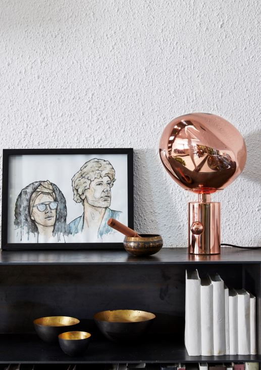 An illustrated image of Craig and Christian, a Copper Melt table lamp by Tom Dixon, porcelain 'books' and a textured wall catch light coming down from skylight.