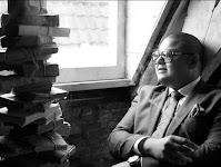 zittende man die tegen een hoge stapel boeken aankijkt op een zolderkamer