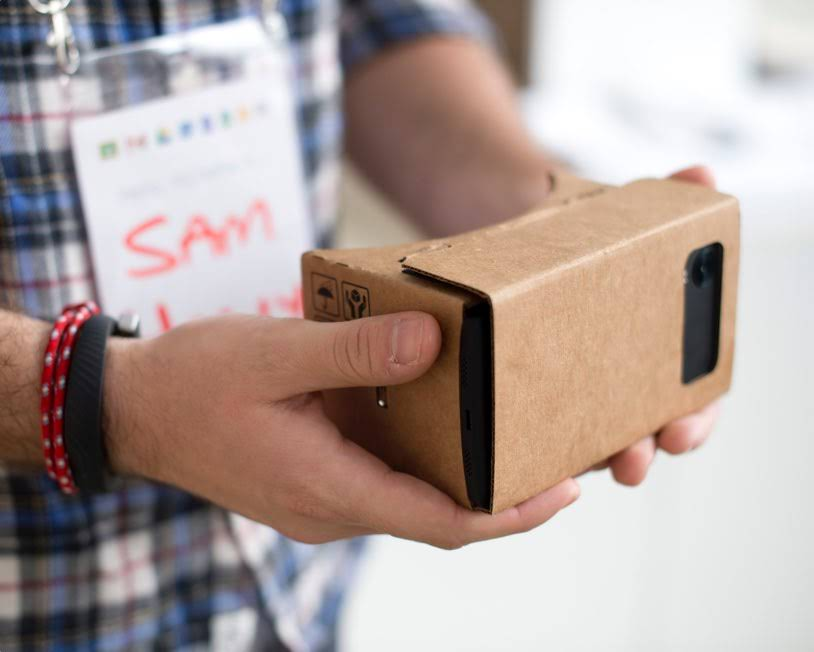 Hands holding a Google Cardboard VR device with phone installed