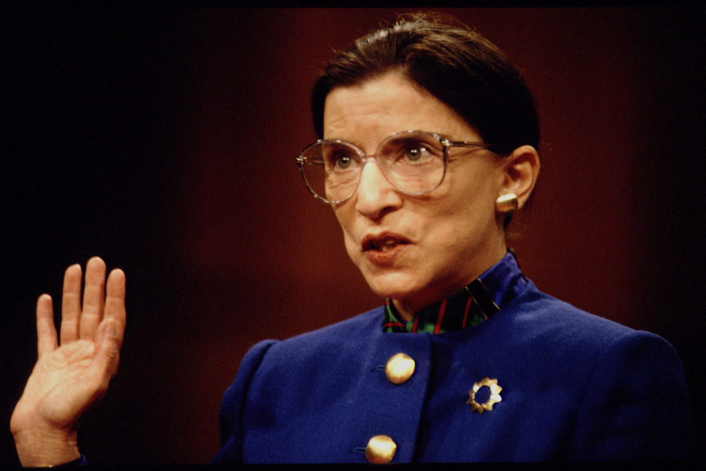 Ruth Bader Ginsburg with her arm raised swearing an oath
