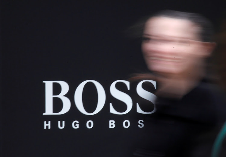 A woman walks past a Hugo Boss store logo in Moscow, Russia. Picture: REUTERS