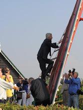 Photo: de minister klimt de wiek in om de zeilen vast te maken