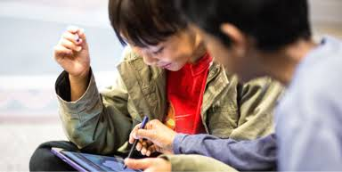 There are two children playing on a tablet, one of them is teaching the other how to use the device.
