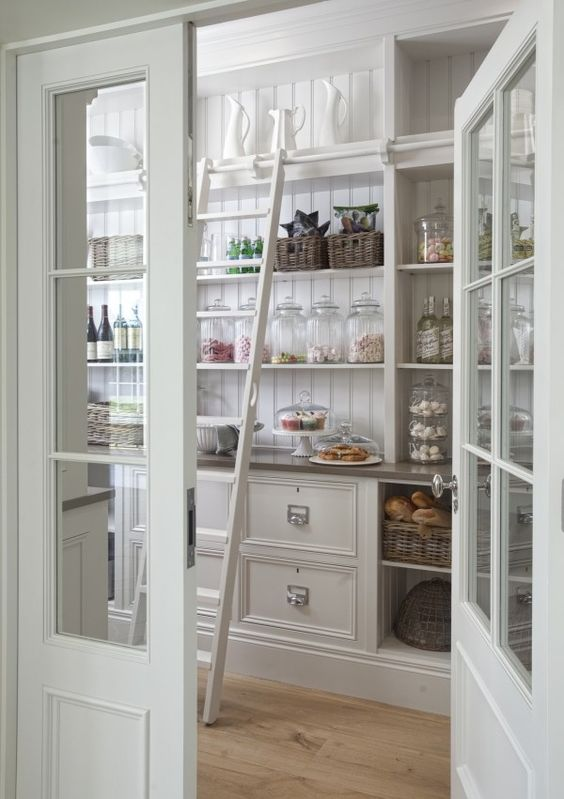 antique white pantry with glass doors, sliding ladder, white cabinets, wood floors, white pantry cabinets