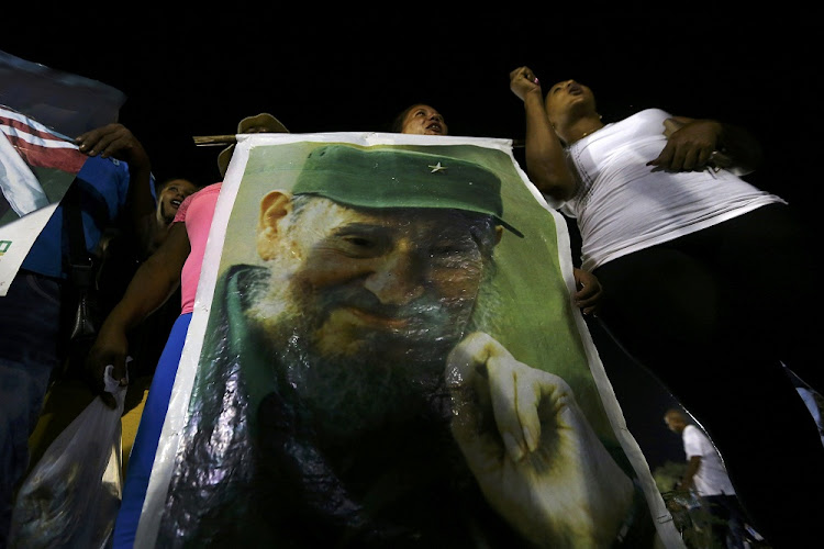 People display an image of former Cuban leader Fidel Castro at a tribute to Castro in Santiago de Cuba, Cuba, on Saturday. Picture: REUTERS