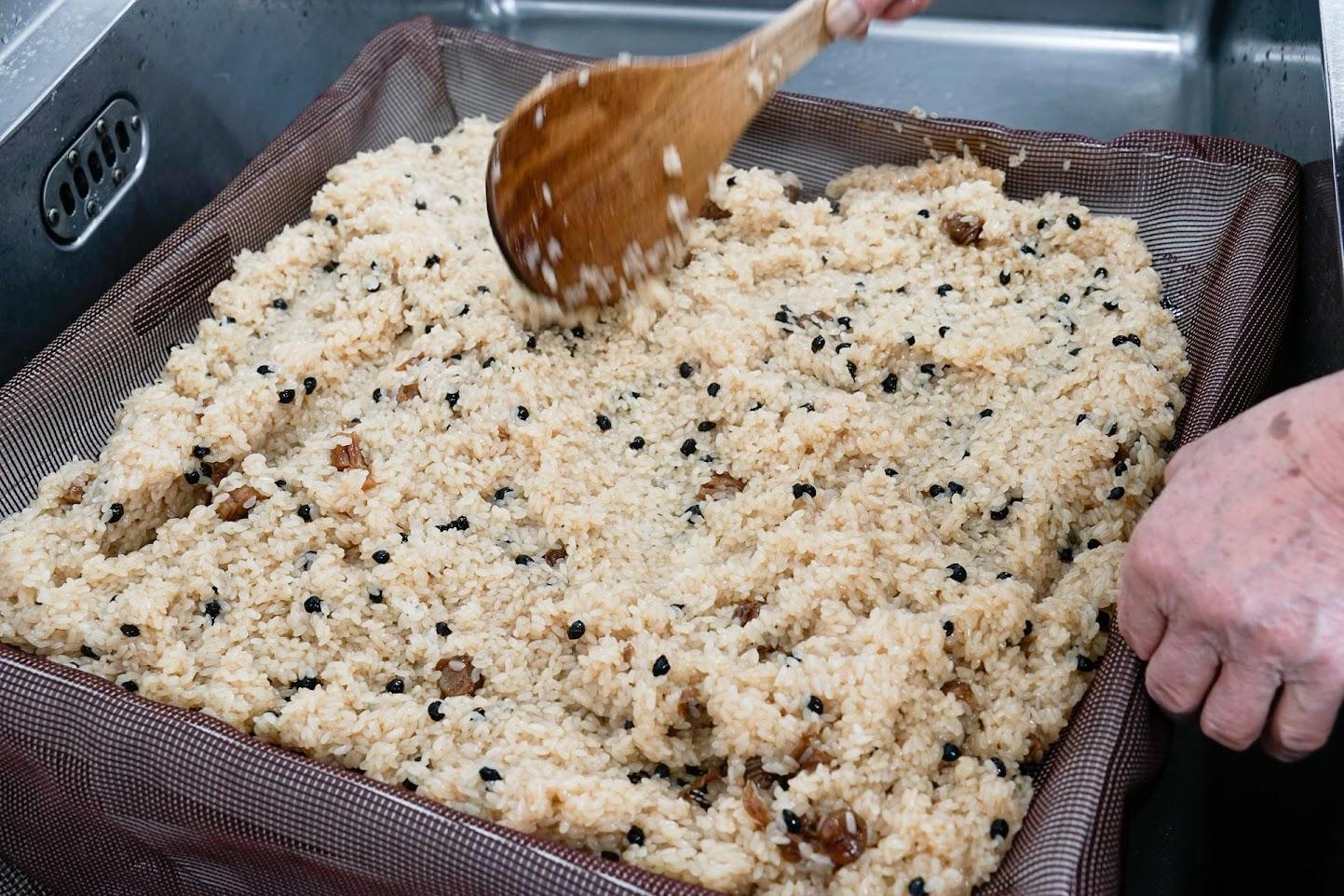 汁を混ぜたもち米を広げ、再び蒸す