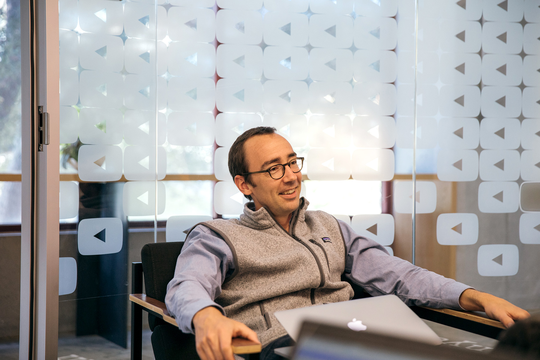 A man in a conference room with the YouTube logo on the wall, smiling and sitting in a chair.