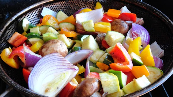 Drained marinated vegetables in basket on the grill