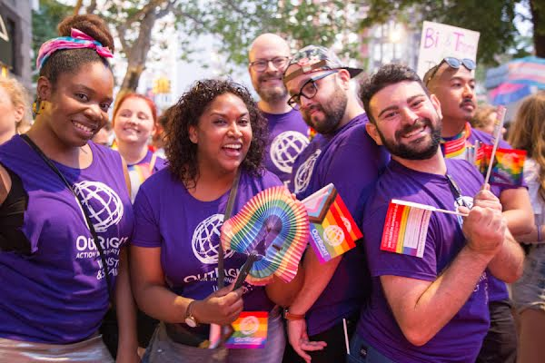 A diverse group of joyful people at an outdoor event wearing purple Outright Action t-shirts, waving Gay Pride rainbow flags