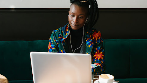 A woman of color with a colorfull jacket sit working on a laptop with earphones on and a coup of coffee at the table