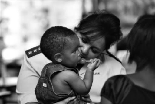 SWEET LOLLY: Captain Julia Claassen with Zanele Radebe during a presentation by the Angels in Blue, a programme by the SAPS that distributes gifts to the orphaned children of police officers, in Rosebank, Johannesburg. Pic: ANTONIO MUCHAVE. 18/12/2009. © Sowetan.