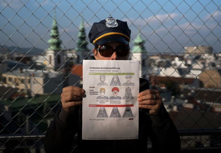 This illustration photo shows a model holding up an information pamphlet about new Austrian restrictions banning the wearing of burqas and other items covering the face in public places and buildings, in Vienna, Austria on September 29, 2017.