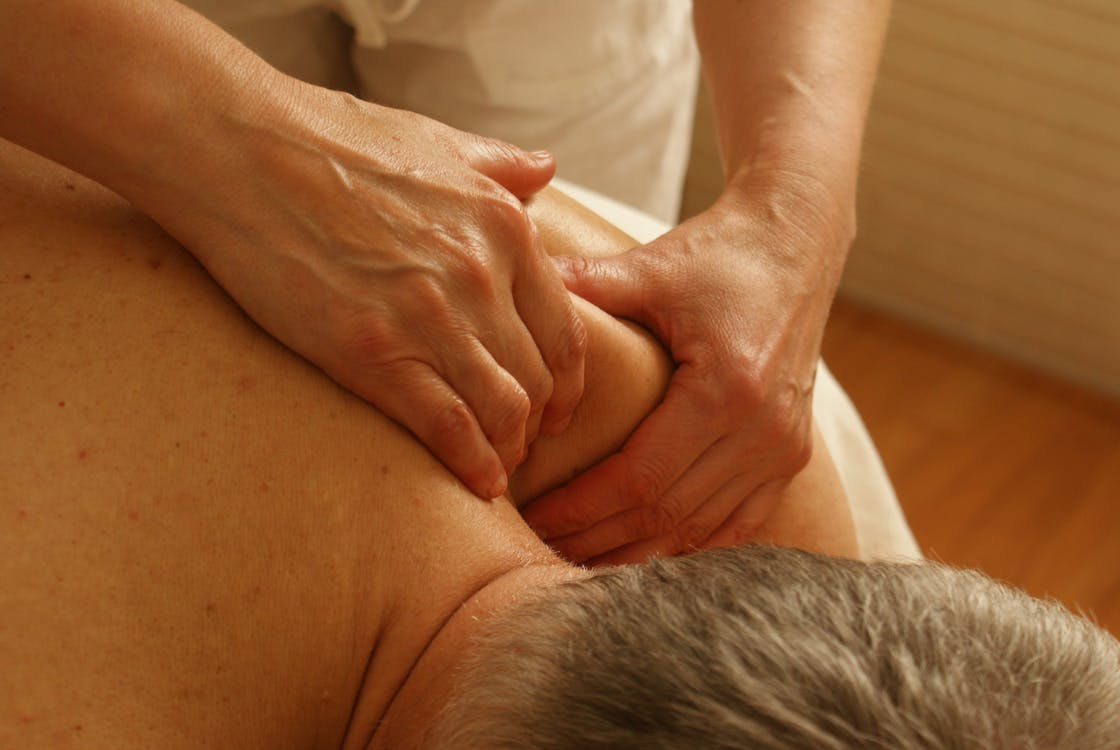Person Massaging Man's Shoulder