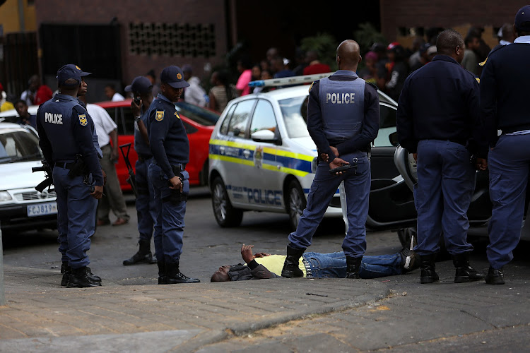 A man lies writhing in pain , after being shot, on Claim Street, in Hillbrow, ​ Johannesburg. A woman is also believed to have been shot in the cross fire. The circumstances of the incident are unclear.