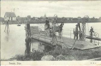 """Photo: 1904 Færgeoverfart ved Stige. Færge blev ført over ved """"rugbrødsmotor"""" - bemærk kaptajnen med rebet på båden."""