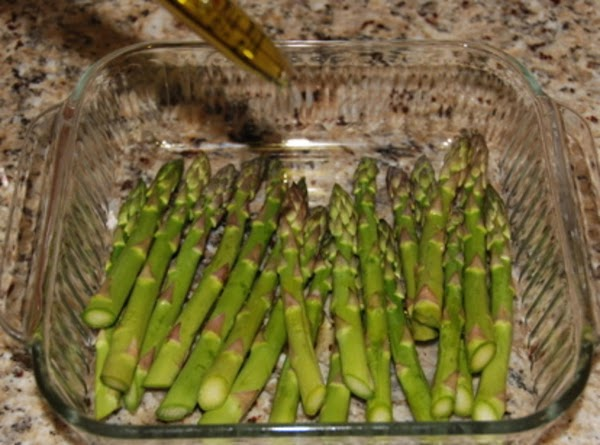 Place in a baking dish and drizzle olive oil over asparagus. Using tongs, roll...