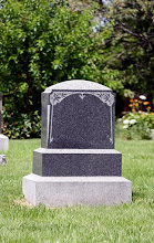 Photo: Blank gravestone headstone backed by bushes and flowers