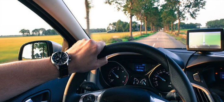 A man wearing a watch driving a car, hand on the steering wheel