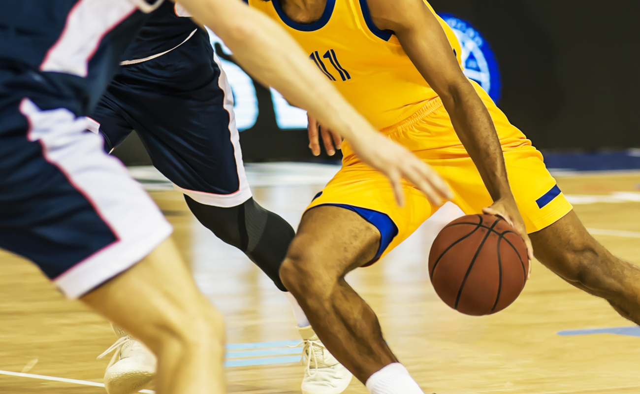 A basketball player in yellow dribbles the basketball between two players