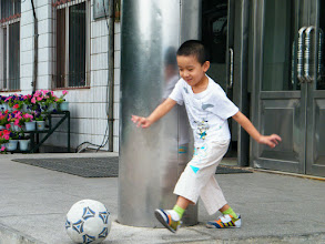 Photo: baby son, warrenzh, 朱楚甲, in a chase of football in the entrance of classroom building of his mom's school.