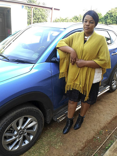 Mmola with her repaired vehicle after the dealer returned it spotless.