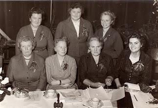 Photo: bestuur 25-jarig bestaan 1956 v.l.n.r. zittend: R. Kamping-Hadderingh, H. van Bergen-Braams, M. Buiter-Hoving en H. Griever-Van Aalderen. Staand: G. Niemeijer-Pepping, W. Dontje-Hoving en A. de Jonge-Meiborg