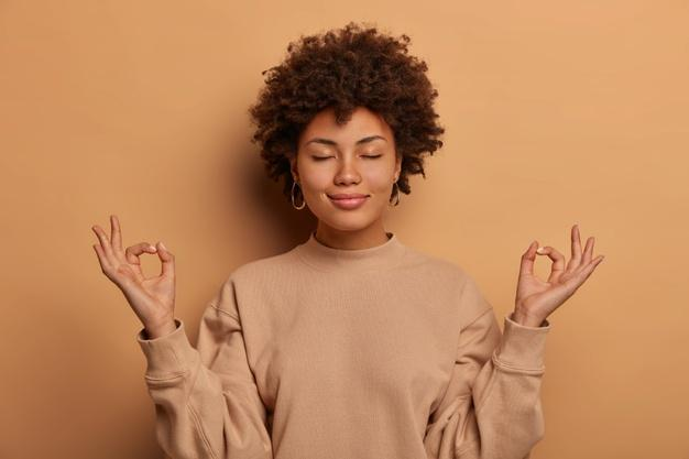 Calm relieved dark skinned woman takes deep breath, keeps hands sideways in zen gessture, reaches nirvana and practices yoga, stands with closed eyes, stands stress free against brown wall Free Photo