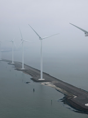 Wind turbines near water, standing on along a thin strip of land in foggy weather.