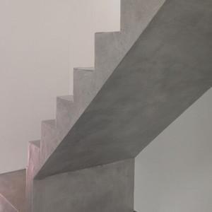 Création d'un escalier sur-mesure en béton ciré avec sous-faice de l'escalier recouvert d'un enduit en béton ciré avec kit prêt à l'emploi