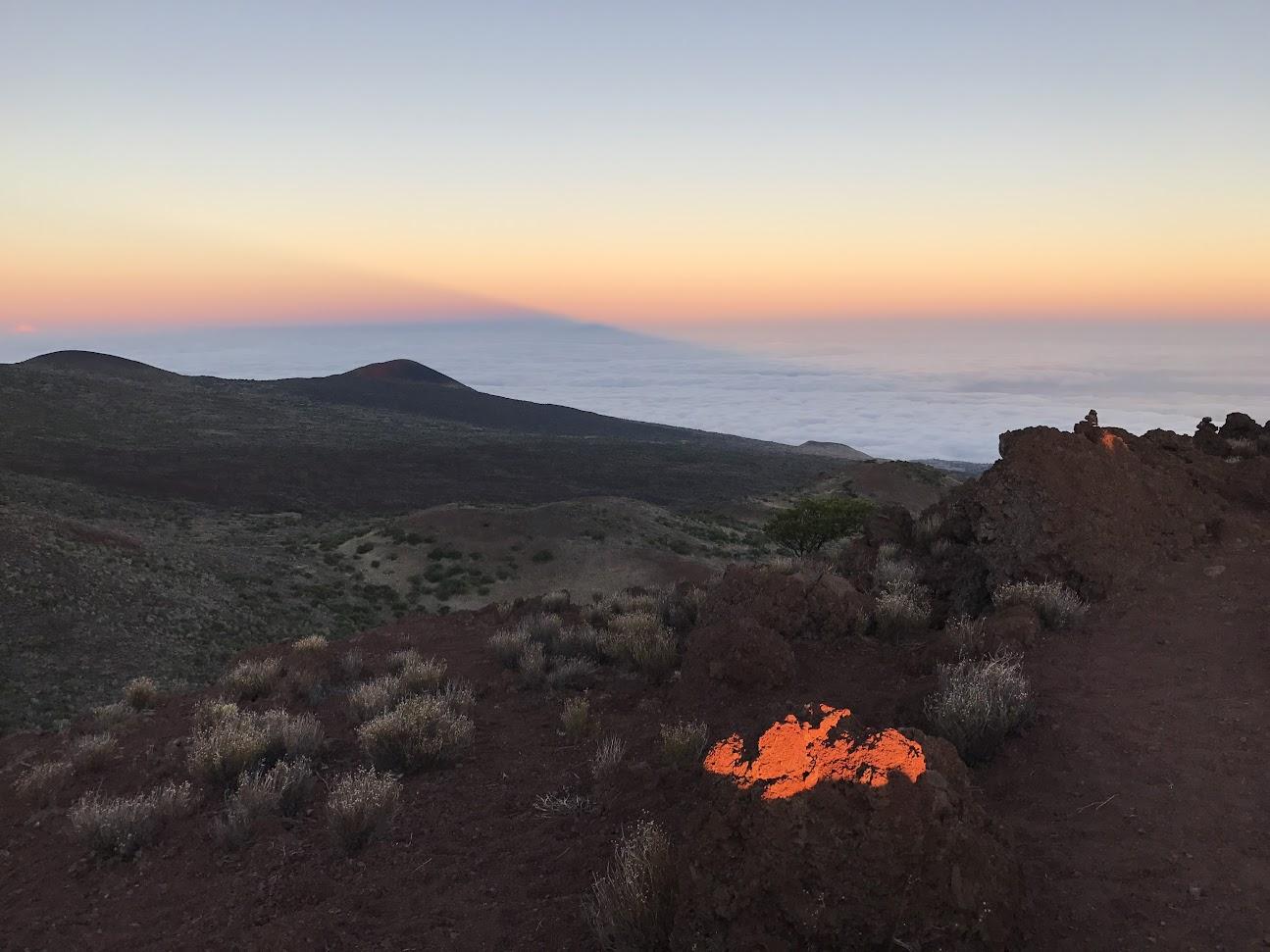 L'ombre du Mauna Kea se projette sur la mer de nuages dans le soleil couchant