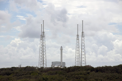 A Falcon 9 rocket with a Dragon capsule secured atop stands upright between the lightning masts on the pad.