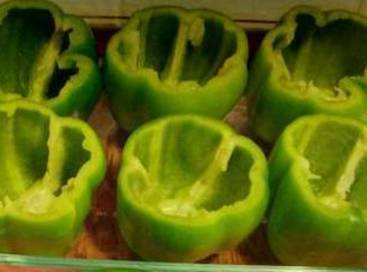 Slice top off of peppers and remove seeds and ribs from inside. Stand up...