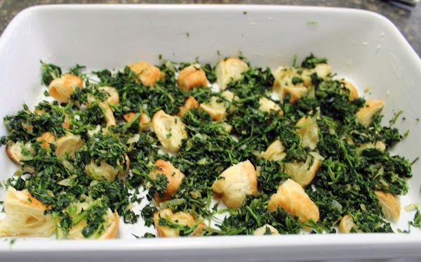 Spinach and onions added to bread cubes in white baking dish.