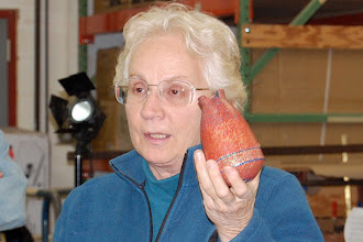 Photo: Tina shows the colored hollow vessel from Mark Gardner's class. (Note the carved feet.)