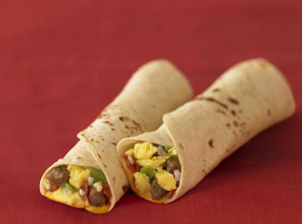 Take a soft burrito and place onto a plate. Add American cheese slice (1-2...