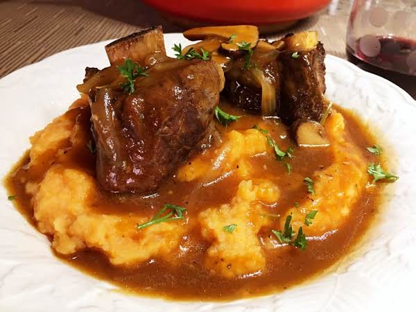 A Couple Short Ribs On A Bed Of Mashed Potatoes.