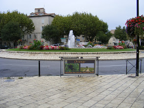 "Photo: Sunday dawns a bit gray, as we've had our first rain of the trip overnight, as we make our way to Orange for the first time. Here, at the fountain and roundabout near the (closed) tourist office, and the sign: ""Orange: Crossroads of the Cote du Rhone Wines."""