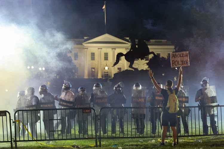 Police in riot gear keep protesters at bay in Lafayette Park near the White House in Washington, US.