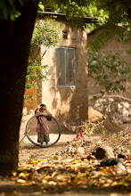 Photo: Village Child, get down to their level Mto Wa Mbu, Tanzania, Africa from the blog http://www.kylefoto.com  Mto Wa Mbu is a village sitting on the edge of one of the greatest natural areas in Africa, the Ngorongoro conservation area. With over 16,000 people in this dense fertile volcanic area, there was a lot to see. I was somewhat apprehensive coming here as I feel that bringing a troupe of photographers and big lenses would be an invasion of privacy, but our tourism is bringing much needed revenue in to bring in fresh water, maintain pipelines and build schools, thus we were welcomed with open arms.  In a world where electricity is often bought a lot like a drink in a bar to power Nokia cell phones that have battery lives of up to two weeks, you aren't going to be seeing children tweeting about how they didn't get an ipad for christmas. I was asked how long the batteries lasted in my Android phone, and they laughed at the idea that I had to charge it almost every night. Tires and soccer balls seem to have a long life here compared to other toys, and most likely have the longest life out of anything else around here.  Photographic details: I was walking with a photographer that has a keen eye for people, while I was photographing some soccer players I noticed my buddy completely change in body posture, kneel down and shoot towards this kid. She had the right idea in getting close to the ground and at the level of the child. Shooting across at them the ground tends to fall out of focus and a much more interesting perspective is achieved. We are so used to seeing everything from eye level that it's no longer an interesting perspective. I like the fact the child is waving, creating a connection between the viewer and the subject. I of course gingerly waved back as this kid smiled, giggled and swung the little tire around as far as his little arms could let him.  1/500s f/2.8 ISO100 200mm