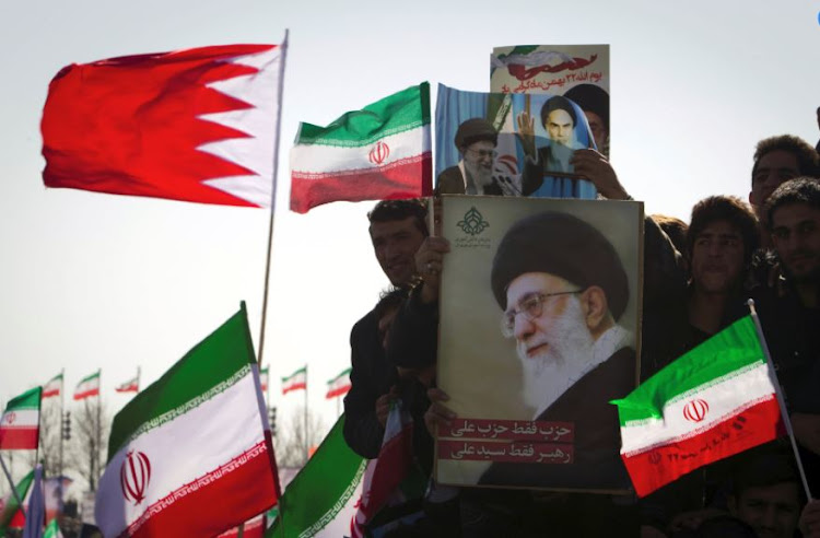 Supporters hold placards of Supreme Leader Ayatollah Ali Khamenei. File photo