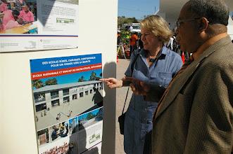 Photo: L'Ambassadeur de Suisse avec le Directeur des Travaux Publics, Alfred Piard, devant les posters des écoles de la coopération suisse.